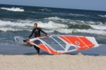 Windsurfer on the beach with board and sail